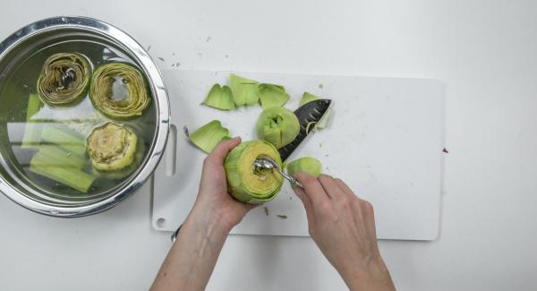 Quitar la mitad superior de las alcachofas, quitar las hojas duras del exterior y quitar el centro. Poner las alcachofas y los tallos en remojo en el agua con limón.