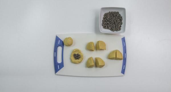 Cortar la masa en ocho trozos, rellenar cada uno con una cucharada de cuadrados de chocolate, cubrir la masa bien sobre el relleno y desplegar en una bola de masa.