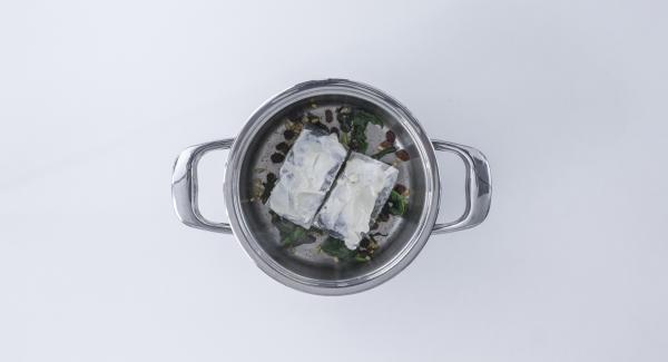 Colocar el bacalao en la olla encima de las espinacas, con el lado del alioli hacia arriba.