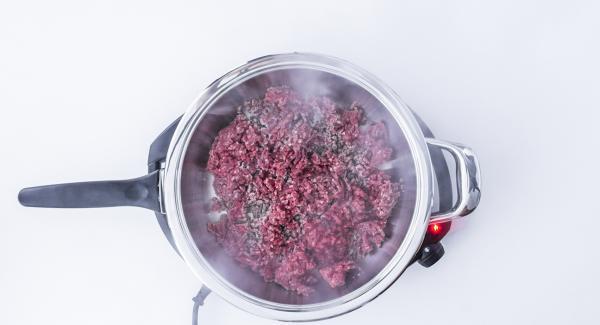 """Cuando el Avisador (Audiotherm) emita un pitido al llegar a la ventana de """"chuleta"""", bajar la temperatura y asar la carne de buey picada hasta que quede crujiente. Añadir los dados de cebolla y ajo y rehogarlo junto. Agregar los dados de tomate y continuar la cocción hasta que el líquido se haya evaporado."""