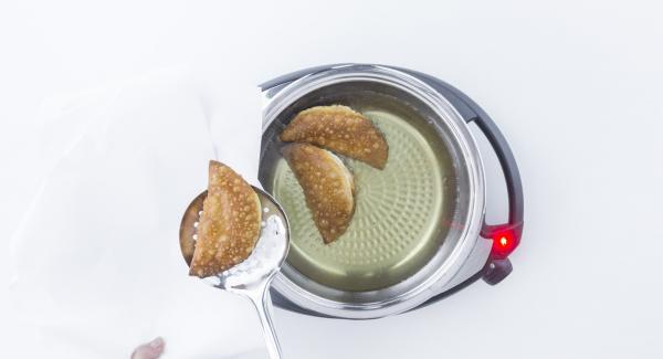 Dejar escurrir las empanadillas ya cocidas sobre papel de cocina y proceder del mismo modo con las restantes.