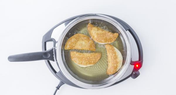 Eliminar la humedad residual que ha quedado en el interior de la tapa utilizando papel de cocina, volver a colocar la tapa y acabar de freír las empanadillas durante un minuto y medio aproximadamente.