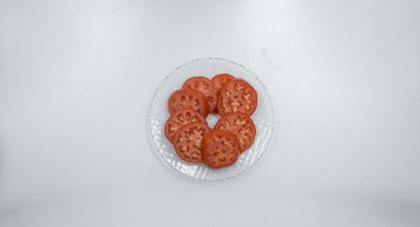 Cortar los tomates a rodajas.