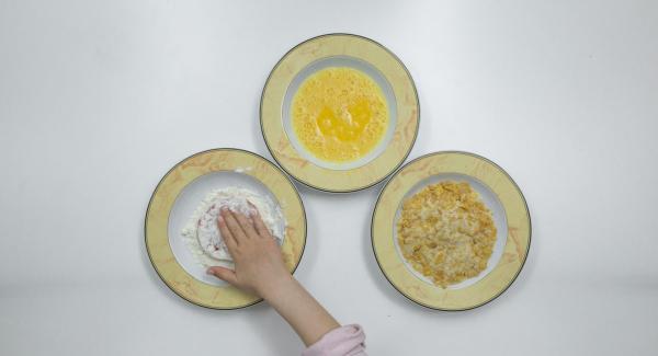 Rebozar las rodajas de tomate primero en harina, después en el huevo y finalmente en la mezcla de copos de maíz y pan rallado.