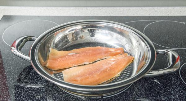 Introducir los filetes de pescado en la paellera con el lado de la piel hacia abajo y colocar la tapa.
