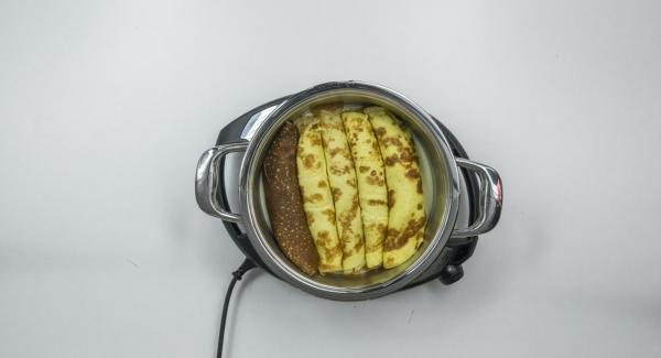 Colocar una olla en el Navigenio caliente. Verter la mitad de la salsa de queso e introducir las crepes rellenas. Agregar el resto de mezcla de zanahorias a la salsa restante y esparcir por encima de las crepes enrolladas.