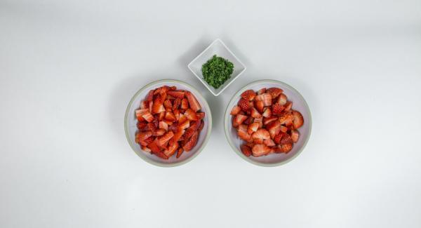 Lavar las fresas y cortarlas en trozos. En una olla, mezclar las fresas con el azúcar para mermelada; quitar las hojas de menta y picarlas finas.