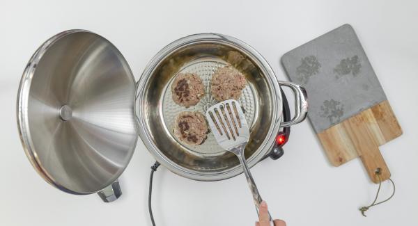"""Cuando el Avisador (Audiotherm) emita un pitido al llegar a la ventana de """"chuleta"""", bajar la emperatura e introducir las hamburguesas, tapar. Freír hasta alcanzar los 90 °C dar la vuelta , volver a tapar y freír por completo con la placa de cocción apagada durante unos 8 minutos."""