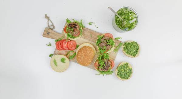 Abrir el pan, calentarlo un poco al gusto y cubrirlo con pesto. Poner una capa de rúcula, tomates y la ternera y servir al momento