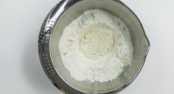 Introducir la harina en un bol y hacer un agujero en el centro, desmenuzar la levadura en el interior. Agregar azúcar y mezclar con un poco de agua y harina, sin dejar de remover, para crear un prefermento. Cubrir y dejar fermentar hasta que el volumen haya aumentado considerablemente. (20 minutos aprox)
