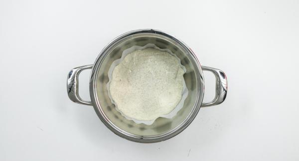 Con la ayuda de una tapa de 24 cm, cortar un círculo del papel encerado. Espolvorear 1 cucharada sopera de harina encima del papel encerado. Con la ayuda de una espátula de amasar, separar la masa del bol y formar una bola de masa. Colocar en el papel encerado y espolvorear con harina. Introducir la masa con el papel en una olla Gourmet.