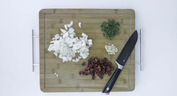 Pelar las patatas, cortarlas en dados y mezclarlas con el aceite de oliva. Pelar la cebolla y el diente de ajo y cortarlos también en dados. Cortar los chorizos en dados y picar las hojas del perejil.