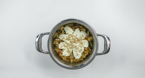 Picar los piñones y cortar el mozzarella en lonchas. Ponerlos encima de la pasta, situar la olla en una superficie resistente al calor