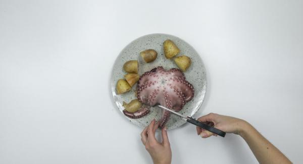 Abrir la tapa y cortar el pulpo y las patatas.