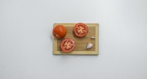 Partir los tomates por la mitad y cortar un extremo del diente de ajo.