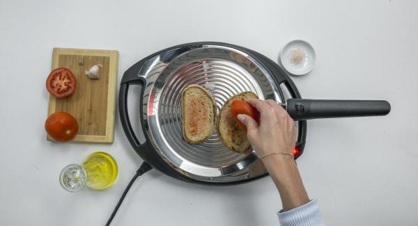 Reducir a baja temperatura, colocar las 2 rebanadas de pan en la oPan y asar por un lado. Dar la vuelta y frotar el pan con el tomate y el ajo.