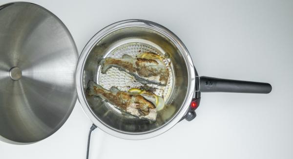 Dar la vuelta al pescado, volver a tapar y asar hasta que esté hecho (unos 3 minutos).