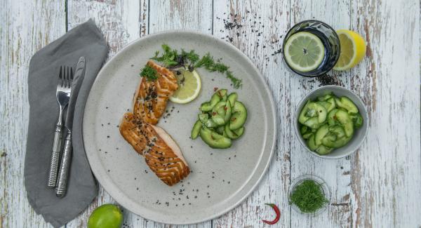 Trocear las hojas de eneldo. Sazonar los filetes de salmón con sal y pimienta, servir con la ensalada de pepino y guindilla, y esparcir el eneldo y el sésamo por encima.
