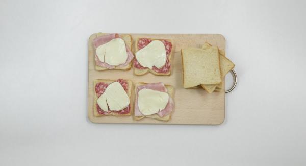 Cubrir media rebanada de pan con el relleno que se prefiera (por ejemplo, lonchas de queso y jamón) y cubrir con la otra mitad del pan.