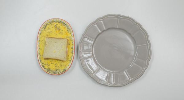 Batir los huevos y la leche con las hierbas. Bañar el pan en la mezcla de huevos y leche.