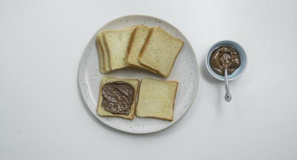 Untar media rebanada de pan con la crema de chocolate y añadir una capa de rodajas de plátano. Cubrir con la otra mitad del pan.
