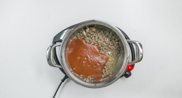 """Cuando el Avisador (Audiotherm) emita un pitido al llegar a la ventana de """"chuleta"""", bajar temperatura de Navigenio (nivel 2) y añadir la carne picada con la mezcla de cebolla y sofreír. Agregar el maíz y los tomates colados, sazonar y mezcle bien."""