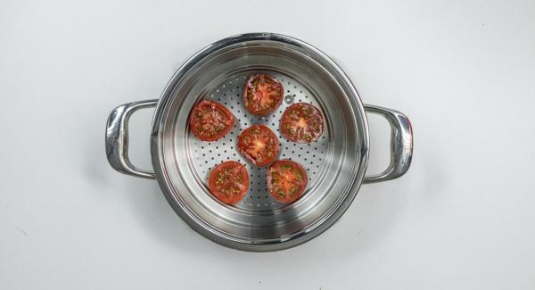 Cortar el tomate horizontalmente en rodajas y colocarlo en el accesorio súper-vapor, rociar con hierbas y extender el queso en cada rodaja con una cucharita.