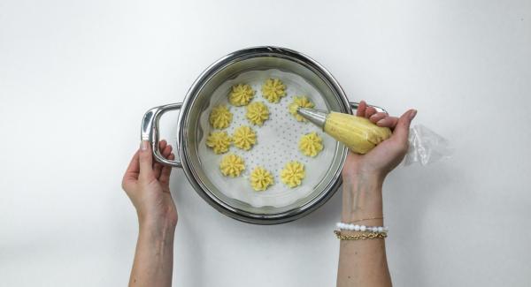 Mezclar las patatas con parmesano, huevo y especias y usando una manga hacer florecitas encima del papel de horno.