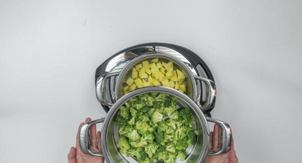 Introducir los dados de patata sin escurrir en una olla y colocar el brócoli en el Accesorio Súper-Vapor.
