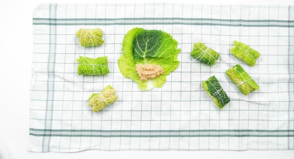 Seca cada hoja de col con un trapo limpio, corta la parte dura central y coloca relleno encima.
