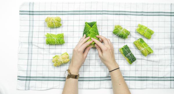 Envuelve la hoja de col formando un paquete. Ata los rollitos con hilo apto para cocinar y colocalos en la softiera 24 cm.