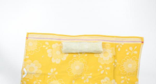 Añadir la mitad de la masa de manzana en el tercio inferior de la pasta de hojaldre, apretar los laterales, enrollar la pasta con la ayuda de un paño e introducirlo en la olla.