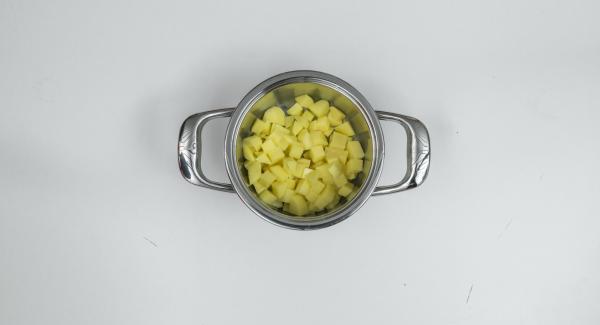 Colocar los cubos de patata con el agua del lavado en una olla y colocar las zanahorias en un accesorio super-vapor sobre ella.