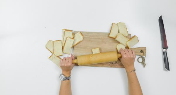 Cortar las rebanadas de pan por la mitad. Estirarlas con un rodillo.