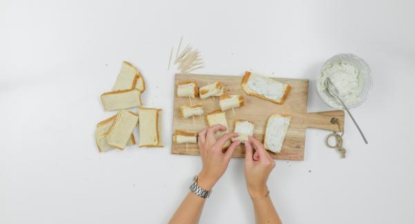 Untar cada tira de pan con un poco de crema de queso, enrollar y fijar con palillos.