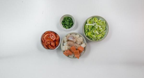 Lavar los puerros y cortarlos a tiras. Quitar y picar las hojas del perejil. Cortar los filetes de pescado a taquitos y salarlos un poco. Lavar los mejillones y quitar las barbas. Desechar los mejillones abiertos. Lavar los tomates y cortarlos a tiras largas.