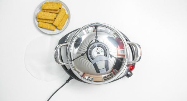 """Cuando el Avisador (Audiotherm) emita un pitido al llegar a la ventana de """"chuleta"""", colocar el papel para hornear en la olla colocando encima las barritas de pescado."""