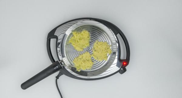 Distruir la masa de patatas en 4 porciones sobre la oPan y presionar ligeramente con una espátula.