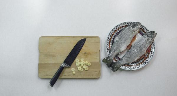 Rellenar la trucha con 2 lonchas de jamón y rebozar en harina. Pelar y cortar los dientes de ajo en rodajas.