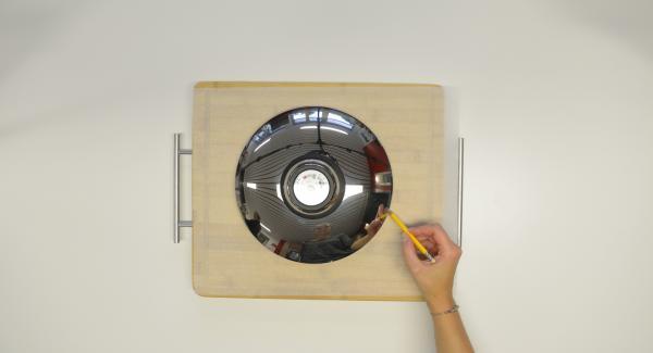 Con ayuda de una tapa de 24 cm, recortar un círculo de papel para hornear.