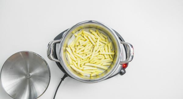 """Cuando el Avisador (Audiotherm) emita un pitido al llegar a la ventana de """"chuleta"""", colocar el papel en el olla y extender las patatas congeladas encima."""