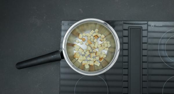 Colocar la Sauteuse en el fuego, introducir el pan cortado en dados y freír a fuego lento hasta que esté dorado.