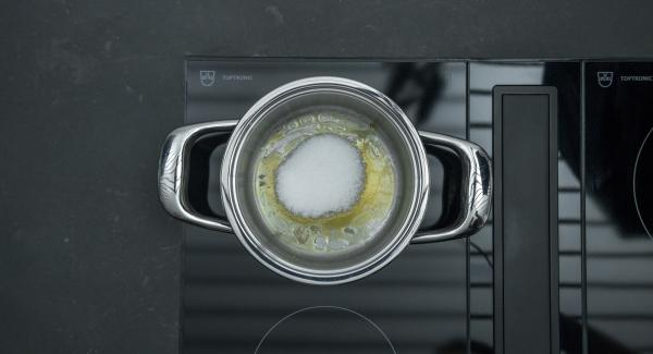 Colocar una olla pequeña con una cucharada de azúcar en el fuego a temperatura máxima. Tan pronto como el azúcar empiece a derretirse y comience a oscurecerse, bajar el fuego y añadir poco a poco 60 g. de azúcar hasta que esté caramelizado.