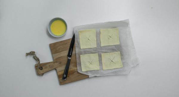 Marcar ligeramente la pasta de hojaldre en el centro con una cruz. Mezclar la yema de huevo y la leche.