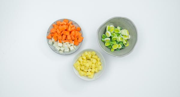 Pelar las patatas, las zanahorias y el nabo. Cortarlos en dados pequeños. Limpiar el puerro y cortarlo en anillos.