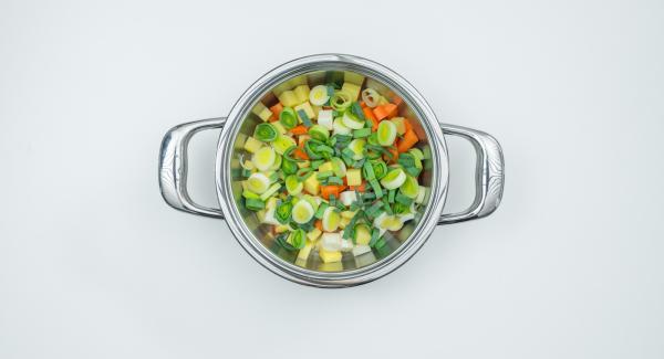 Introducir los dados de patata, zanahoria y nabo en la olla, sin escurrir, añadir los anillos de puerro y los dados de tomate.