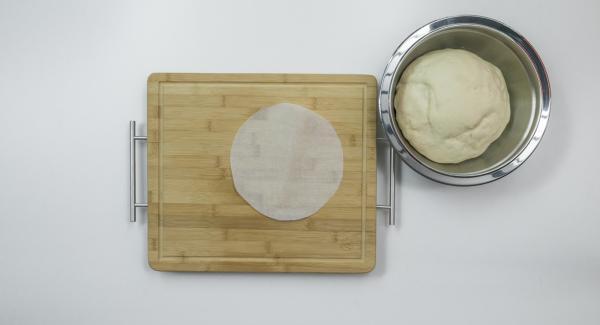 Formar un pan redondo con la masa y marcar ligeramente la superficie con unos cortes. Con la ayuda de una tapa de 20 cm. cortar un círculo de papel para hornear.