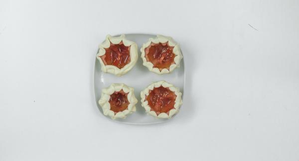 Extender la masa de pizza finamente y cortar círculos ligeramente más grandes que el tomate. Por ejemplo, con un vaso. Enrollar bien los círculos de masa alrededor del tomate doblando un poco la masa por el borde superior.
