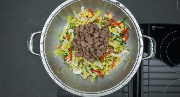 En el mismo Wok freír las verduras sin dejar de remover, añadir de nuevo la carne y sazonar con sal y pimienta.