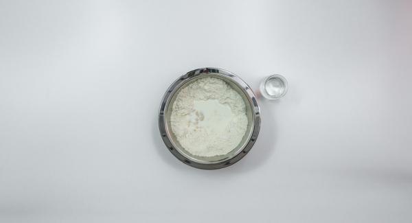 Añadir la levadura, el azúcar, el agua y la leche. Disolver la levadura mientras se revuelve y mezclar con un poco de harina.